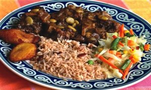 Jamaican Oxtail dish served with vegetables, plantains and rice and peas