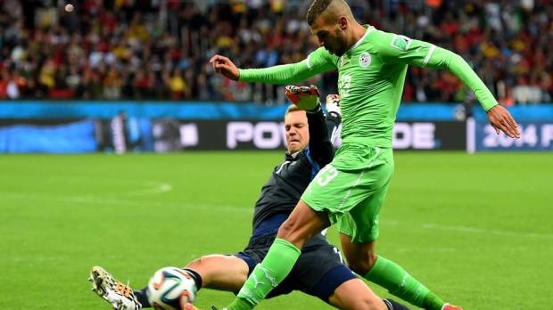 2014 FIFA World Cup - Algeria forward Islam Slimani is tackled by Germany goalkeeper Manuel Neuer.