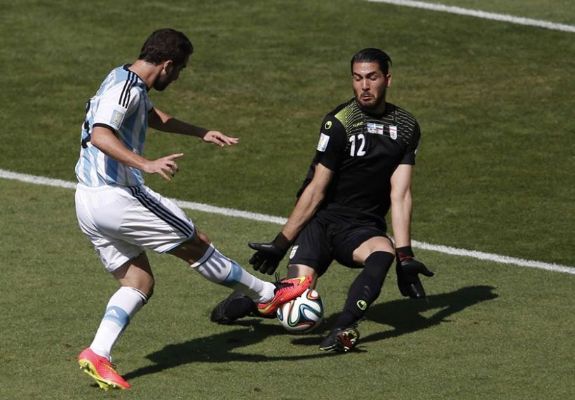 2014 Fifa World Cup - Argentina's Gonzalo Higuain fails to get the ball past Iran's goalkeeper Alireza Haqiqi