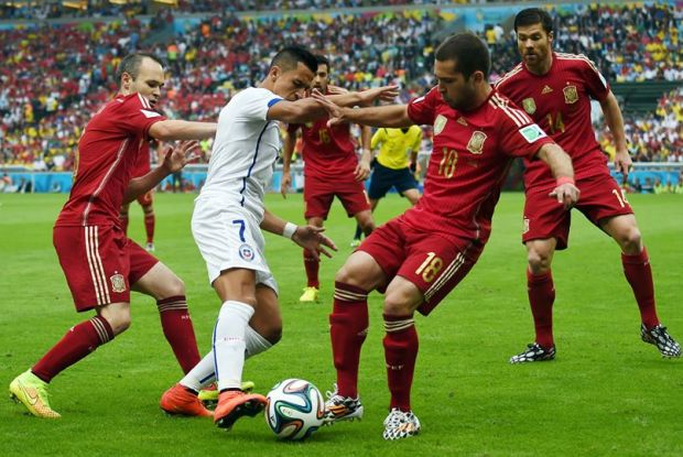 Chile's Alexis Sanchez attempts to dribble past Spain's Jordi Alba and Andres Iniesta - Spain 0 vs. 2 Chile
