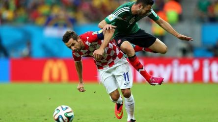 2014 FIFA World Cup - Croatia captain Darijo Srna challenges Mexico's Miguel Layun for the ball.