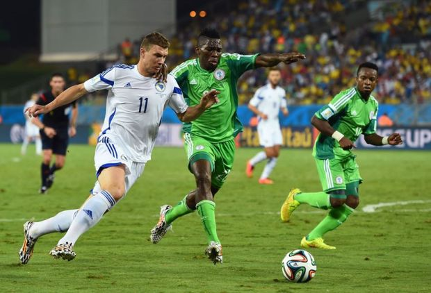 Edin Dzeko of Bosnia and Herzegovina and Kenneth Omeruo of Nigeria compete for the ball during the 2014 FIFA World Cup