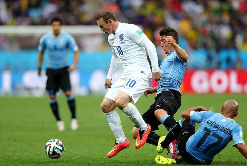 2014 FIFA World Cup - England's Wayne Rooney holds off challenges from Uruguay's Cristian Rodriguez and Edigio Arevalo.