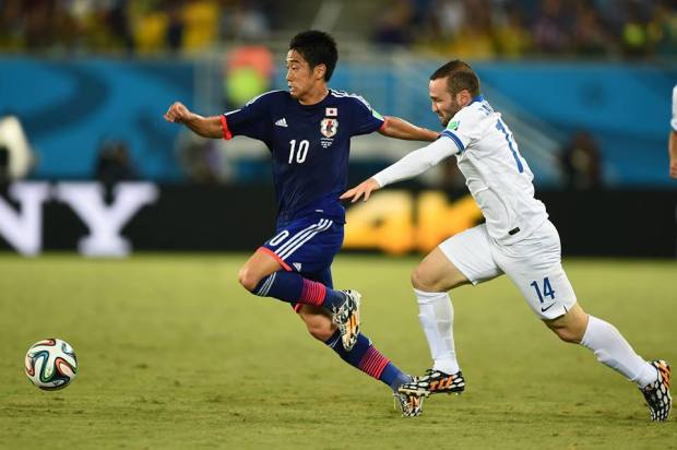2014 FIFA World Cup - Japan's Shinji Kagawa dribbles past Greece's Dimitrios Salpingidis.