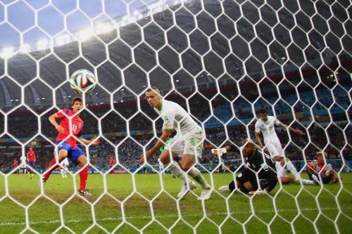 2014 FIFA World Cup - Koo Ja-Cheol of South Korea (L) scores his team's second goal past Djamel Mesbah and goalkeeper Rais M'Bolhi of Algeria