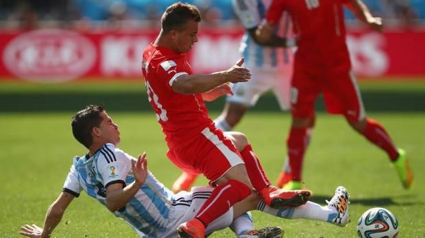 2014 FIFA World Cup - Argentina midfielder Fernando Gago tackles Switzerland's Xherdan Shaqiri.